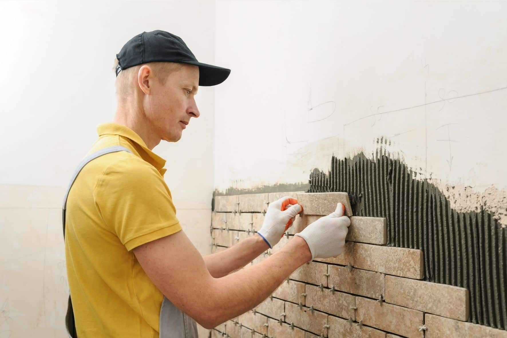 A Geelong Tiler employee in yellow uniform installing brick tiles on a wall